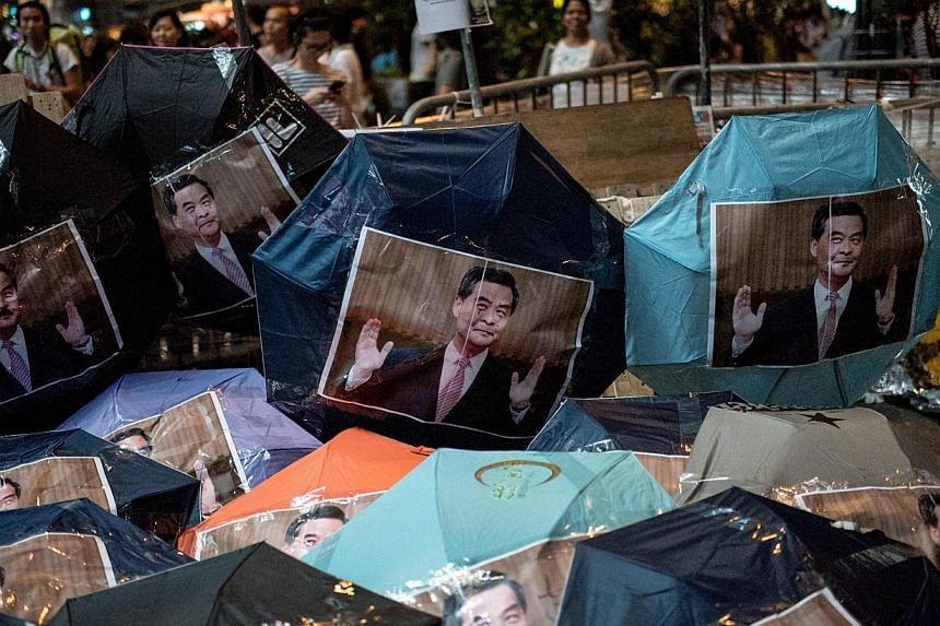 Images of Hong Kong Chief Executive Leung Chun-ying are pasted onto umbrellas -- symbols of the Hong Kong pro-democracy protests -- at a barricade set up in the Mongkok district of Hong Kong on Oct 18, 2014.Historyrarely moves in ways sim