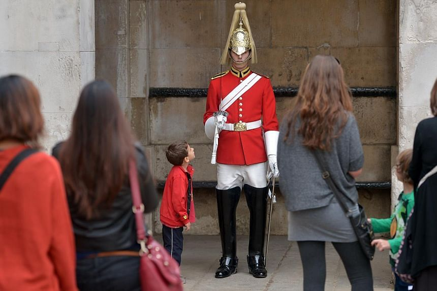 Tourists watch a soldierperforming sentry duty on Sept 10, 2014, at Horse Guards Parade in London.Armed soldiers have been deployed at the top tourist attraction in the heart of London's government district as a precautionary measure afte