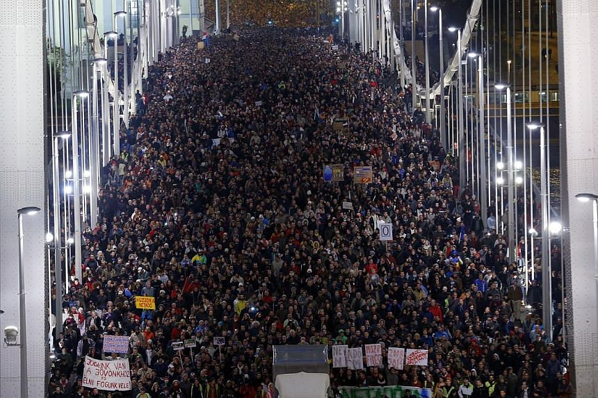 Ten of thousands of Hungarians march across the Elisabeth Bridge during a protest against a new tax on Internet data transfers in centre of Budapest, Oct 28, 2014. -- PHOTO: REUTERS
