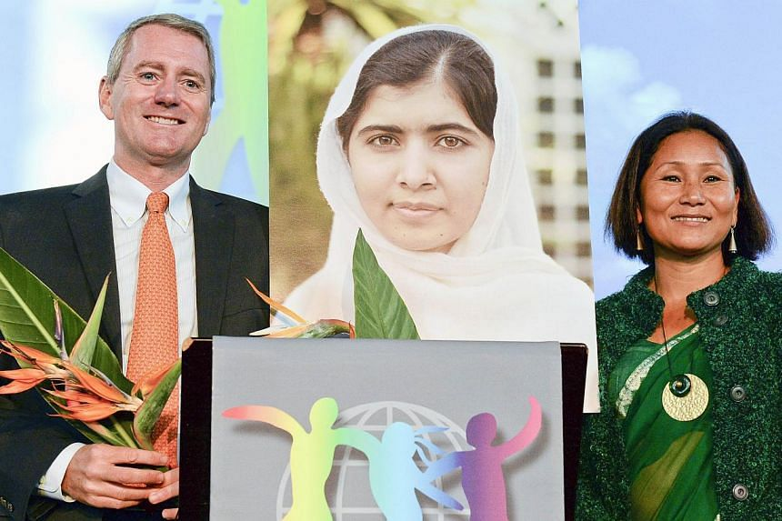 A picture of 2014 World's Children's Prize for the Rights of the Child winner, Malala Yousafzai of Pakistan stands next to World's Children Honorary Award winners John Wood of the US (left) and Indira Ranamagar of Nepal during a press conference on O