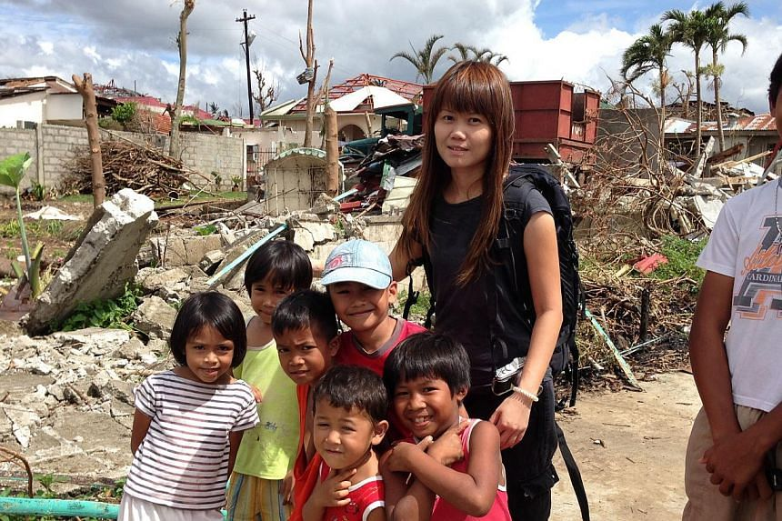 Straits Times correspondent Joyce Lim with young survivors of the devastating typhoon that struck the Philippines in 2013.-- PHOTO: ST FILE