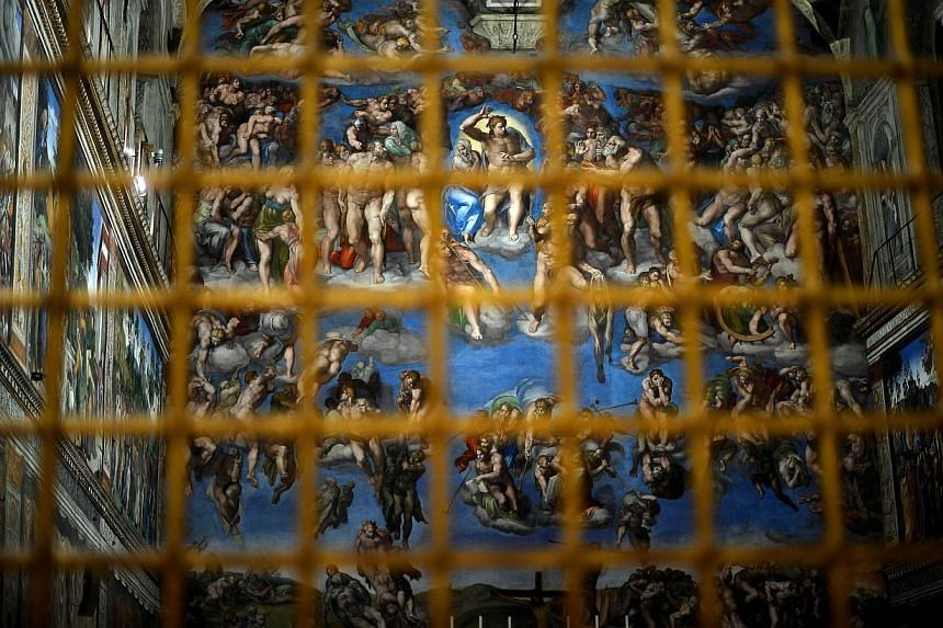 The Sisitne Chapel with its new lighting is seen through a fence during a press visit at the Vatican on Oct 29, 2014. High above the altar in the Vatican's Sistine Chapel, the halo around Jesus Christ's head in Michelangelo's famous frescoes shi