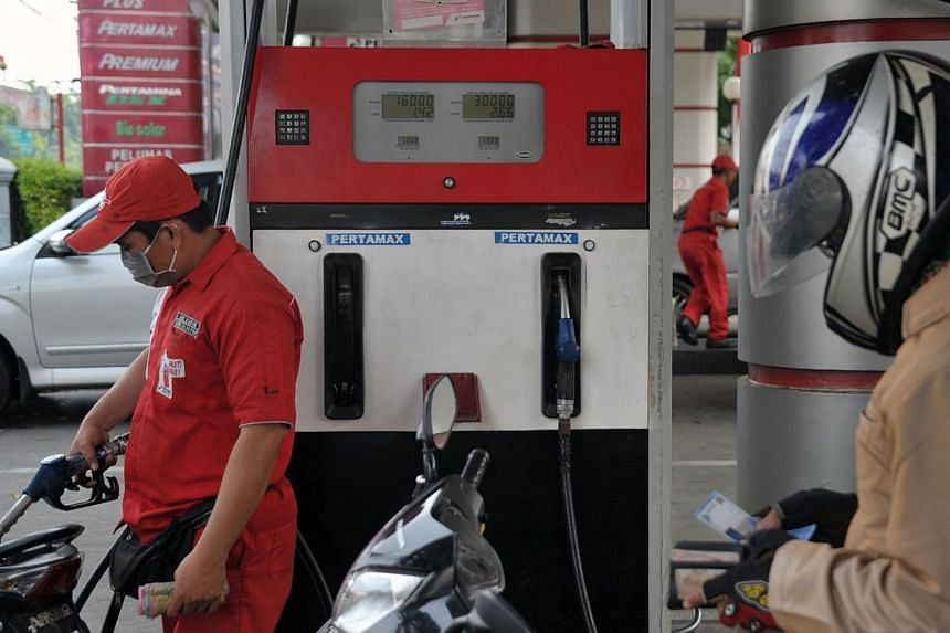 A worker (left) filling a motorcycle with non-subsidised gasoline at a fuel station in Jakarta on Aug 29, 2014. Indonesia's new government will make changes to its costly gasoline and diesel subsidies before the end of the year, the country's ch