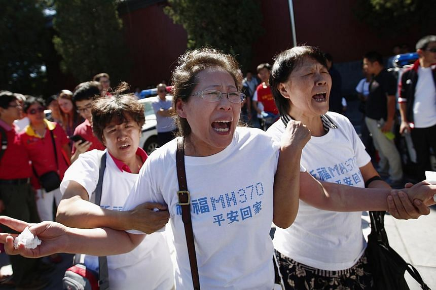 Anguished family members of MH370 passengers gathering to pray at a temple in Beijing on Sept 8, six months after the tragedy.