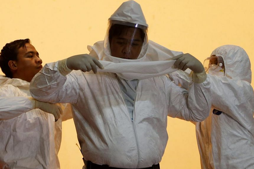 Philippine health workers assist a colleague to don a hazmat suit during a media tour displaying the government's measures in preparing against Ebola at the Research Institute for Tropical Medicine Hospital, at Alabang, Muntinlupa on Oct 21, 2014. --