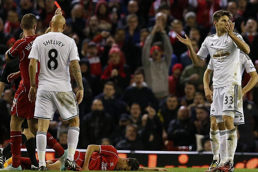 Swansea City's Federico Fernandez (right) reacts after being shown a red card during their English League Cup soccer match against Liverpool at Anfield in Liverpool, northern England, on Oct 28, 2014. -- PHOTO: REUTERS