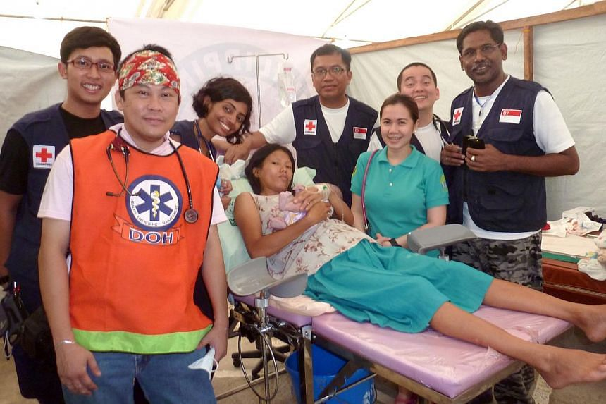 Dr Meera Ravindran (third from left), a medical officer with the Singapore General Hospital's department of renal medicine, with the mother of a baby boy that she helped delivered when she volunteered to help earthquake victims in Bohol, Philippine