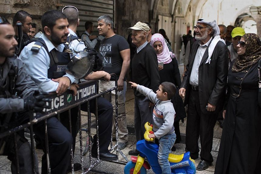 Israeli border policemen prevent Palestinians from entering the Al-Aqsa mosque compound in the old city of Jerusalem on Oct 30, 2014 after Israeli authorities temporarily closed it. -- PHOTO: AFP