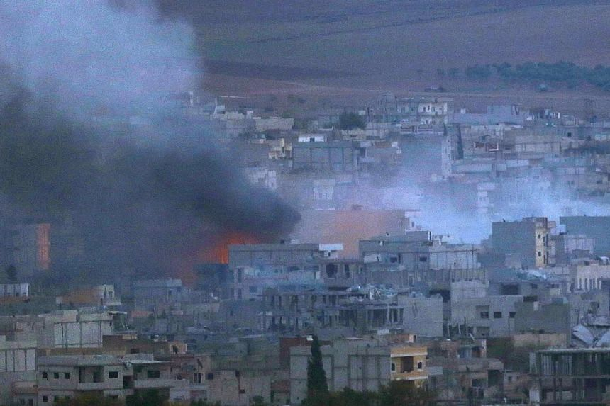 A fire burns in the Syrian town of Kobane during heavy fighting between Islamic State in Iraq and Syria (ISIS) militants and Kurdish Peshmerga forces on Oct 27, 2014. Foreign Islamic fighters from more than 80 countries have flocked to fight in