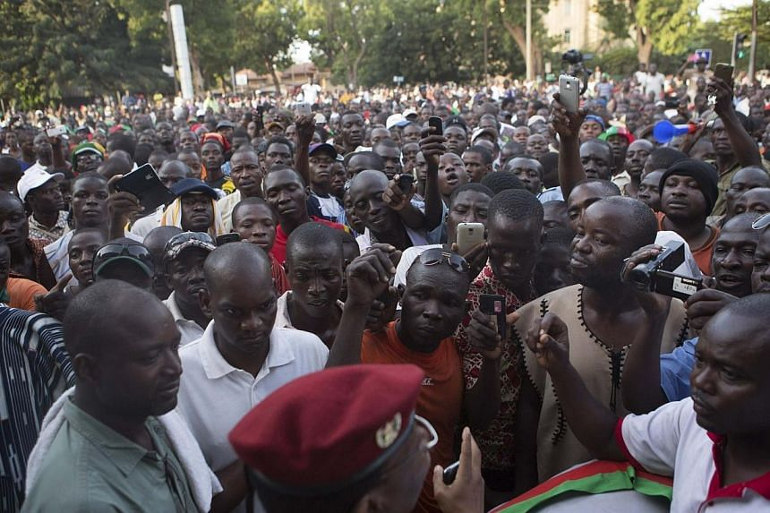 An army spokesman speaks to anti-government protesters outside the military headquarters in Ouagadougou, capital of Burkina Faso on Oct 30, 2014.Tens of thousands of people took to the streets of Burkina Faso on Friday to press President Blaise