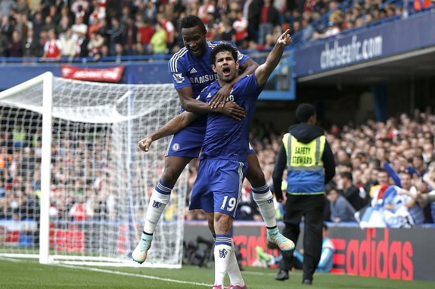 Chelsea's Brazilian-born Spanish striker Diego Costa celebrates scoring their second goal with Chelsea's Nigerian midfielder John Obi Mikel (up) during the English Premier League football match between Chelsea and Arsenal at Stamford Bridge in London