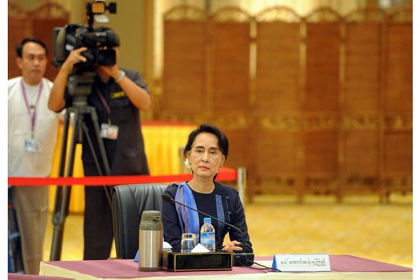 Aung San Suu Kyi (centre), chairman of National League for Democracy (NLD) and lower house member of Parliament arrives prior to her meeting with Myanmar President Thein Sein (not pictured) at the president's resident office in Naypyidaw on Oct 31, 2