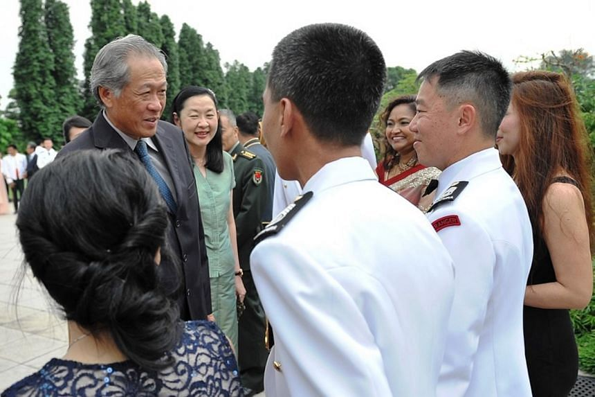 Minister of Defence Dr Ng Eng Hen interacting with graduands and their spouses at the Command and Staff Course 2014 Graduation Ceremony.  -- PHOTO: MINDEF