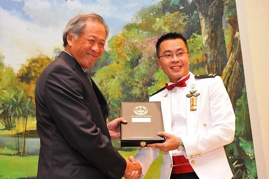 Dr Ng presenting the top Army graduate award to Major Koh Poh Hui during the presentation ceremony. -- PHOTO: MINDEF