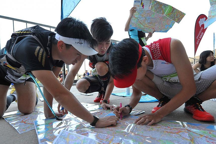 Participants of the Nathan Singapore City Race this year checking maps to look for five checkpoints. The event had categories with distances from 5km to 45km and attracted 4,000 people this year. -- PHOTO: PINK APPLE