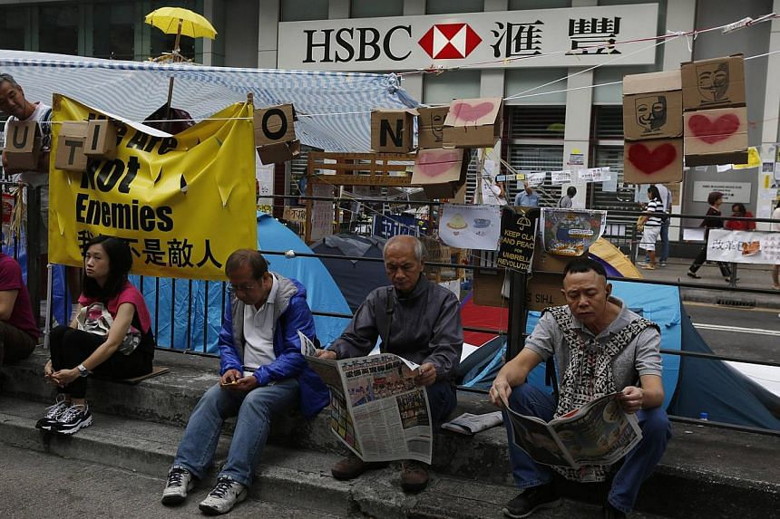 People reading newspapers outside an HSBC branch closed since the start of an Occupy movement at Mongkok shopping district in Hong Kong on Oct 16, 2014. Thousands have signed an online petition denouncing reported comments by HSBC Holdings board memb