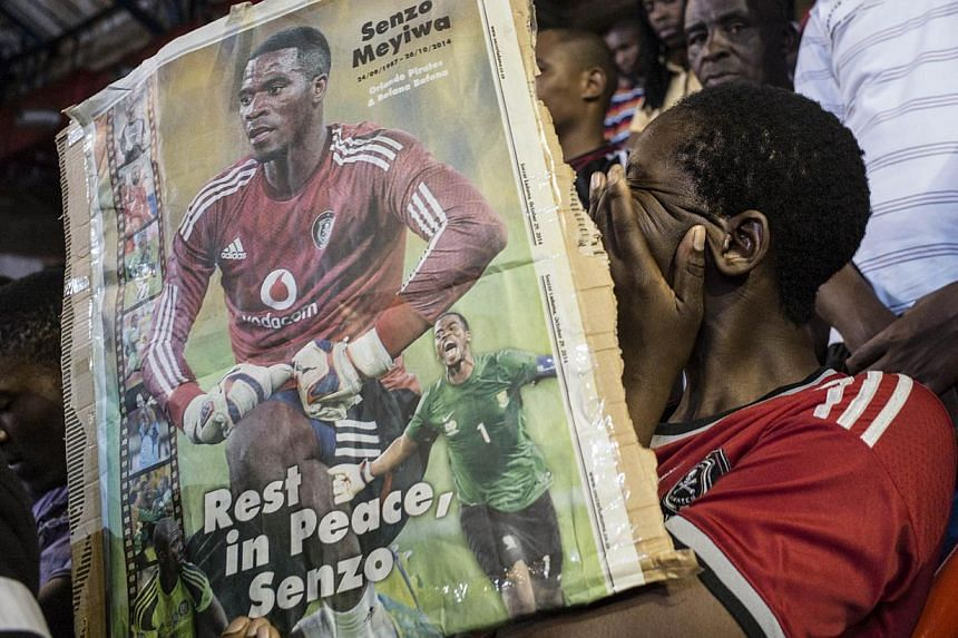 A fan cries holding a portrait of slain South African football captain Senzo Meyiwaduring a memorial service in Johannesburg on Oct 30, 2014.A suspect appeared in court on Friday over the murder of Meyiwa, whose death during a robbery has