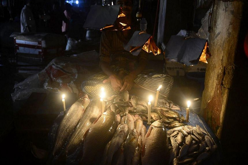 A Bangladesh fishmonger lights his fish stall with candles during a power blackout in Dhaka on Nov 1, 2014. -- PHOTO: AFP
