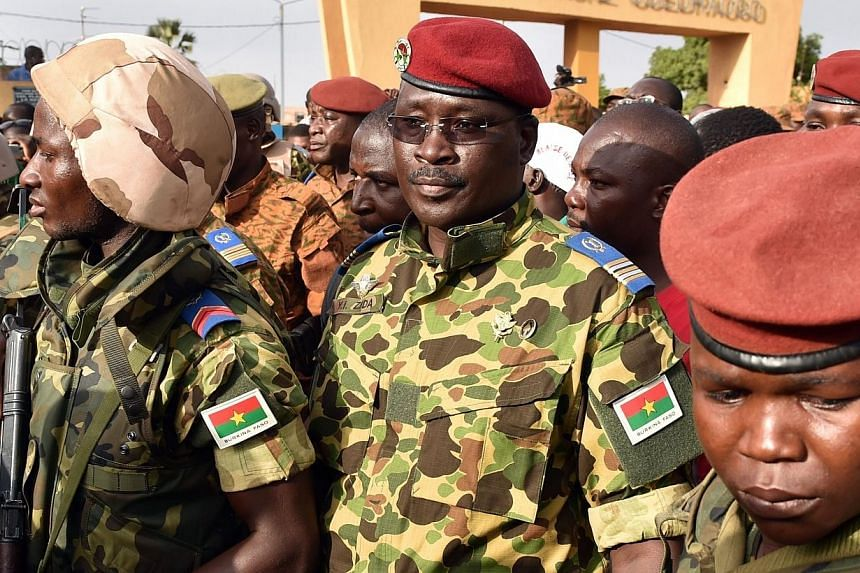 Burkina Faso's army on Saturday backed Lieutenant-Colonel Isaac Zida (centre) to lead a transition period after the ousting of president Blaise Compoare. -- PHOTO: AFP