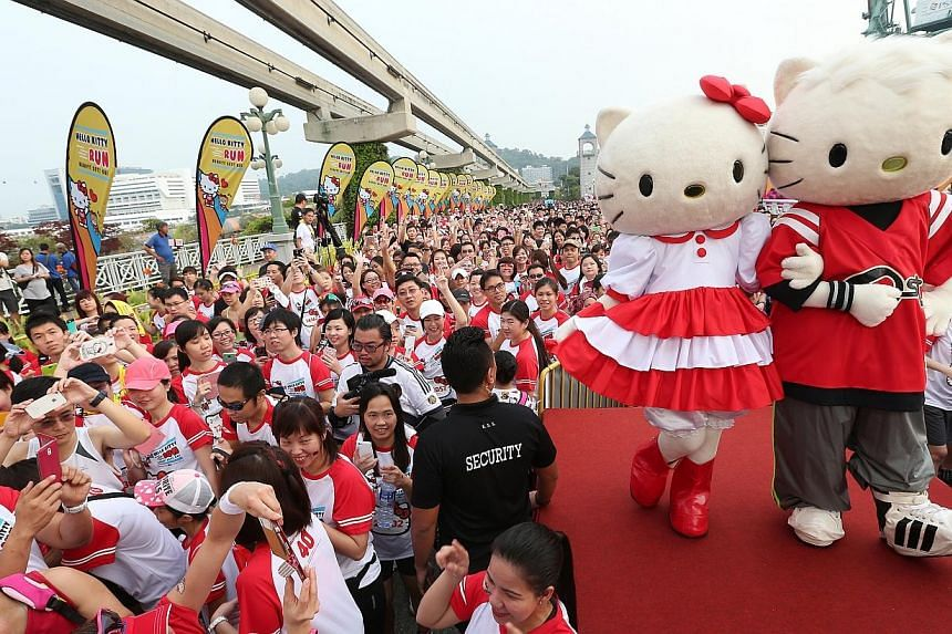 Race participants stop to take photographs of Hello Kitty and Dear Daniel on stage after they flagged off the first wave of runners at 8am. -- ST PHOTO: NEO XIAOBIN