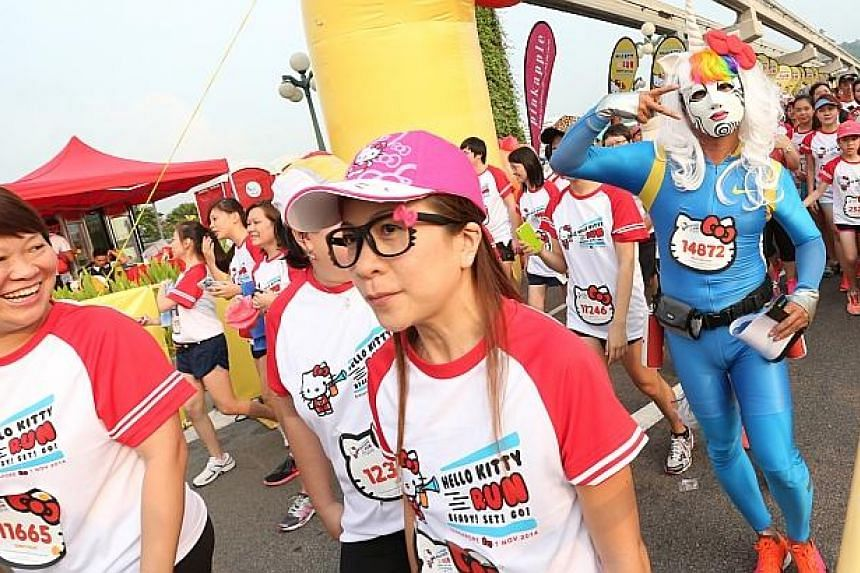 A man dressed as an unicorn get stares from fellow race participants at the start of the Hello Kitty Run Singapore. -- ST PHOTO: NEO XIAOBIN