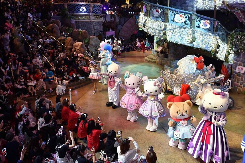 Hello Kitty (fourth right) and her twin sister Mimmy (fifth right) perform with Sanrio characters in the Hello Kitty 40th anniversary parade at Tokyo's Sanrio Puroland on Nov 1, 2014. -- PHOTO: AFP