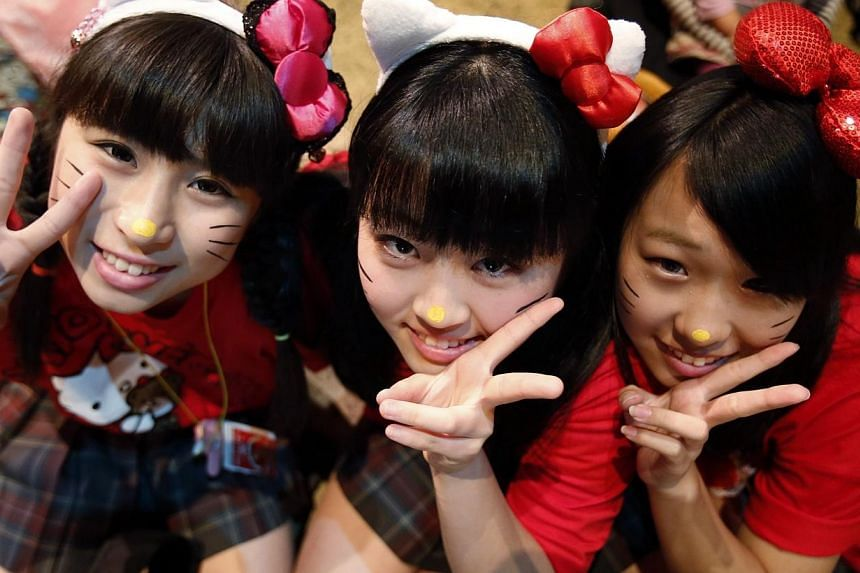 Visitors wearing make-up and hairbands to resemble Hello Kitty, pose during an event to celebrate her 40th birthday at Sanrio Puroland theme park in Tokyo on Nov 1, 2014. -- PHOTO: REUTERS