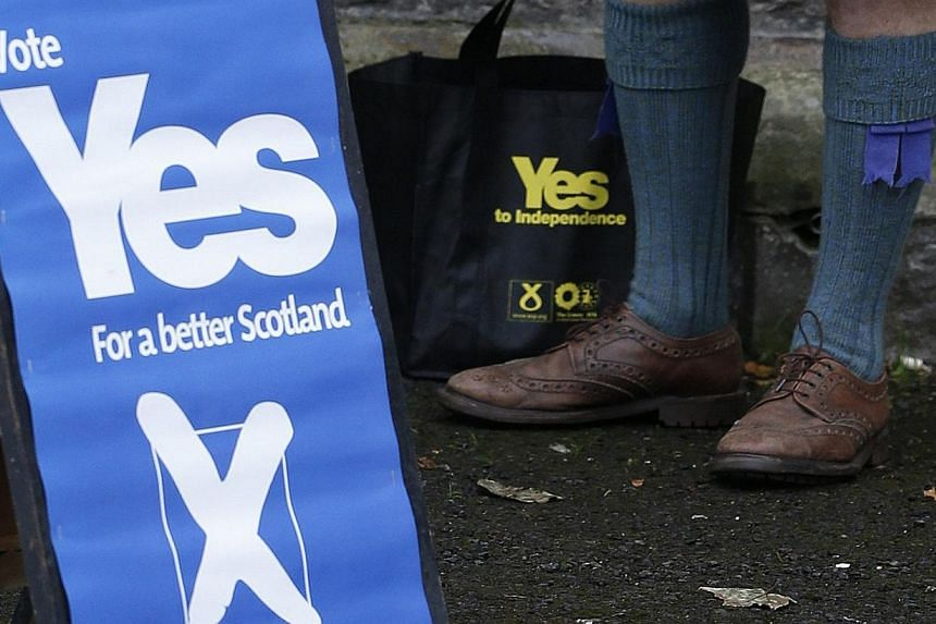 A supporter of the 'Yes' campaign stands outside a polling station during the referendum on Scottish independence in Pitlochry, Scotland on Sept 18, 2014. A majority of Scots would back independence if another referendum were held today, according to