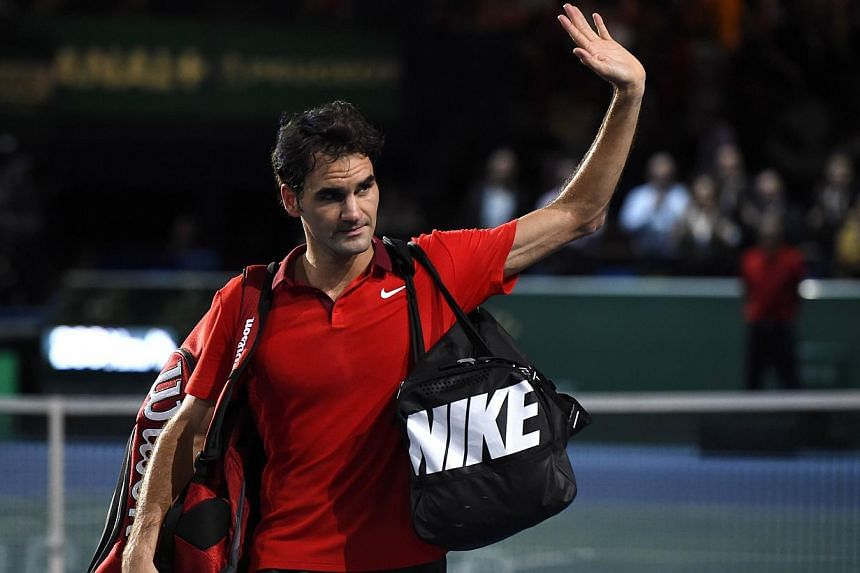Switzerland's Roger Federer waves after his defeat against Canada's Milos Raonic during a quarter-final match at the ATP World Tour Masters 1000 indoor tennis tournament on Oct 31, 2014 at the Bercy Palais-Omnisport in Paris. -- PHOTO: AFP