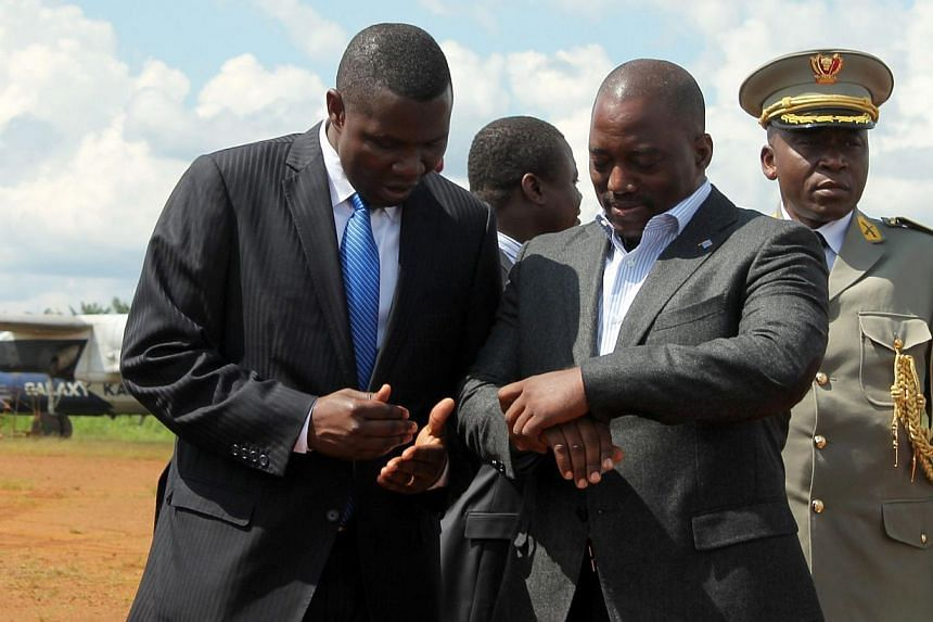 Congolese President Joseph Kabila (centre) checks his watch on Oct 29, 2014 as he arrives at the Mavivi airport in Beni, some 12kms north of the eastern city of Goma, an area where over 80 civilians were killed with machetes by Ugandan-based Allied D