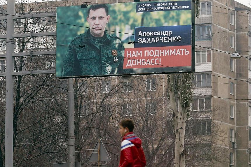 A man walks past an election information board with portrait of Alexander Zakharchenko, separatist leader of the self-proclaimed Donetsk People's Republic, in Donetsk, eastern Ukraine, Nov 1, 2014. -- PHOTO: REUTERS