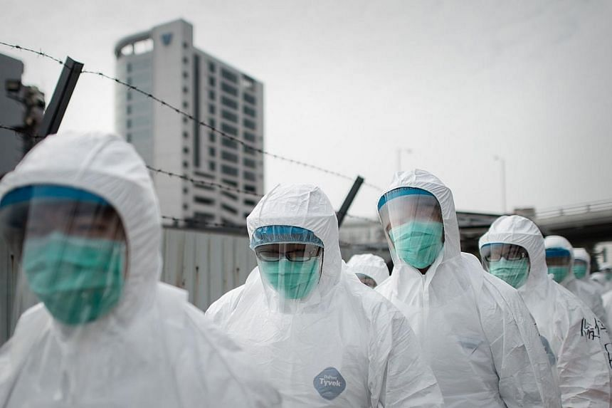 Officials wearing masks and protective suits proceed to cull chickens in Hong Kong, as Hong Kong began a mass cull of 20,000 chickens after the deadly H7N9 bird flu virus was discovered in poultry imported from mainland China, on Jan 28, 2014. Asia's