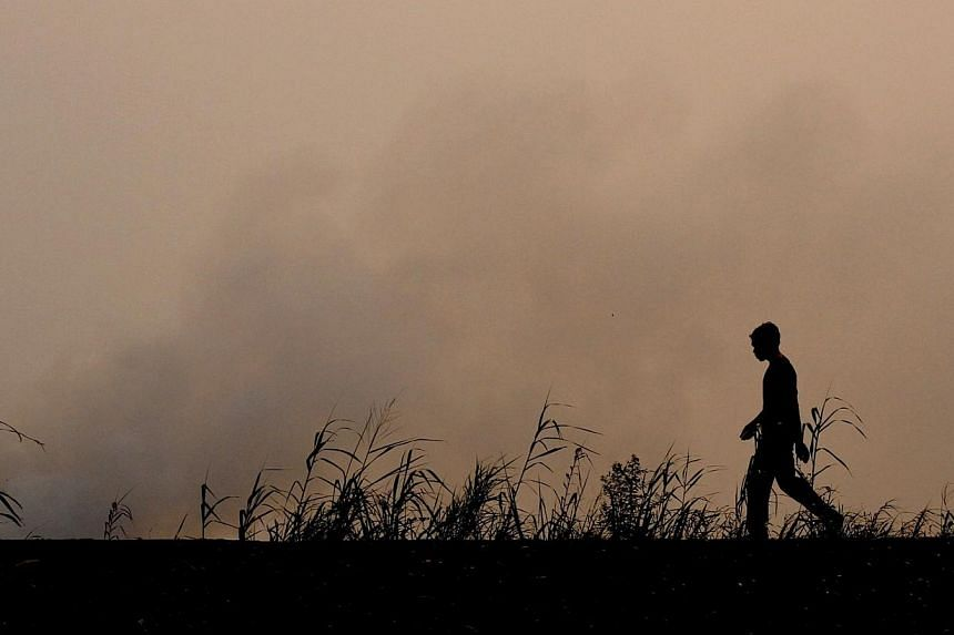 This picture taken in Ogan Ilir on Sept 11, 2014 shows an Indonesian firefighter walking on farm land where fire was raging in Ogan Ilir, South Sumatra. Haze from forest and plantation fire in Central Kalimantan and South Sumatra have intensifie