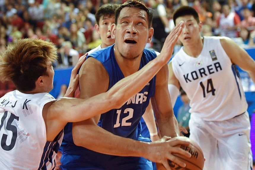 June Mar Fajardo of the Philippines (centre) competes with Kim Jong-Kyu of South Korea (left) during their men's quarter-final group H basketball match at Samsan World Gymnasium Ground during the 17th Asian Games in Incheon on Sept 27, 2014.The
