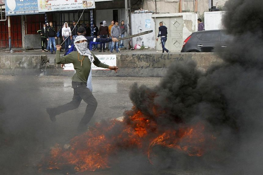 A masked Palestinian protester uses a sling shot to throw stones at Israeli troops, during clashes following an anti-Israel demonstration over the entry restrictions to the Al-Aqsa mosque, at Qalandia checkpoint near the West Bank city of Ramallah Oc