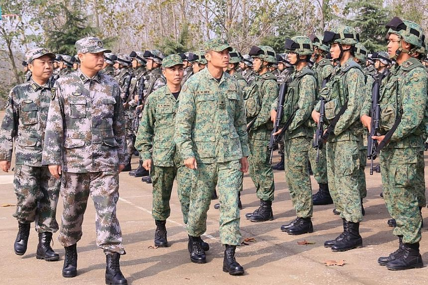 Brigadier-General Siew Kum Wong(2nd left, foreground) and Major-General Wang Chunning(left, foreground) with the exercise troops. -- PHOTO: MINDEF