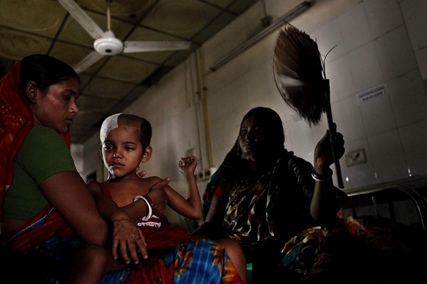 A Bangladesh woman fans a sick child during a power blackout at a hospital in Dhaka on Nov 1, 2014.Power was restored in most parts of Bangladesh late on Saturday, some 12 hours after a massive nationwide electricity blackout hit the country, p