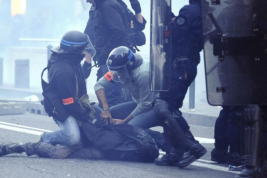 Police officers arrest a protester during clashes following a demonstration in memory of Remi Fraisse, who died in the early hours on Oct 26 during violent clashes between security forces and protesters against a controversial dam project, in Toulous