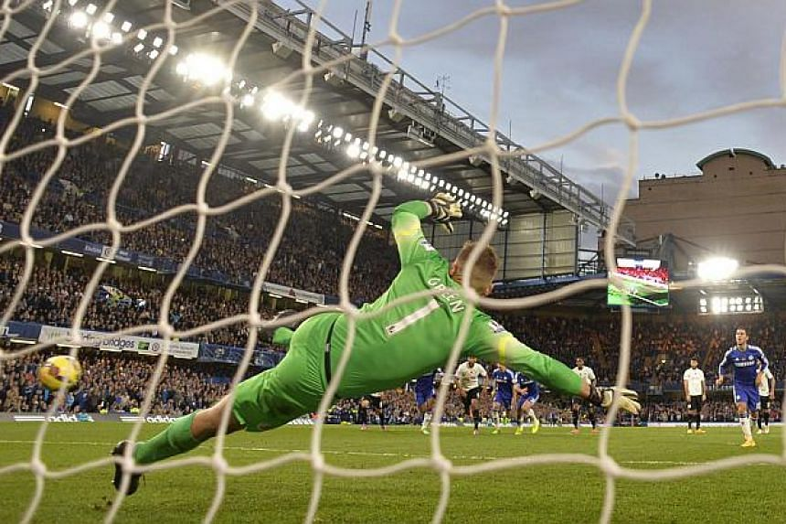 Chelsea's Eden Hazard (right) shoots to score a penalty against Queens Park Rangers during their English Premier League soccer match at Stamford Bridge in London Nov 1, 2014. Hazard's penalty enabled Chelsea to preserve their four-point lead in the P
