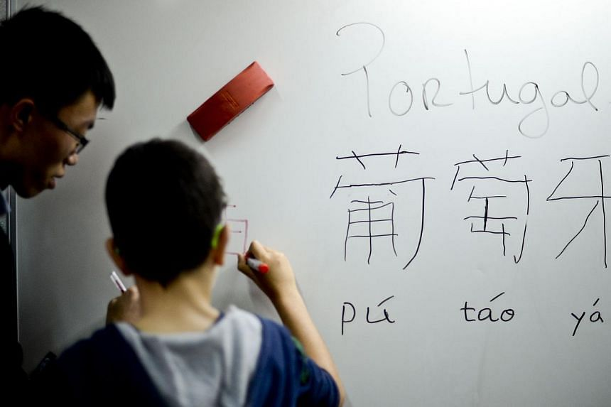 Professor Wang Xin Liang checks a pupil's writing on a board during a Chinese class at Parque School in Sao Joao da Madeira on Oct 13, 2014.-- PHOTO: AFP