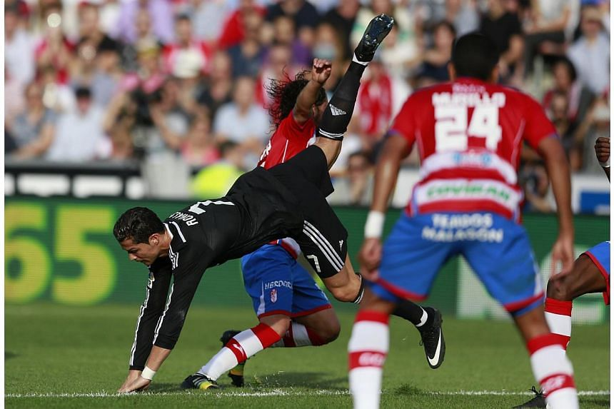 Real Madrid's Cristiano Ronaldo is tackled by Manuel Iturra during their Spanish First Division soccer match at Nuevo Los Carmenes stadium in Granada, Nov 1, 2014. Real Madrid moved to the top of La Liga for the first time this season as goals