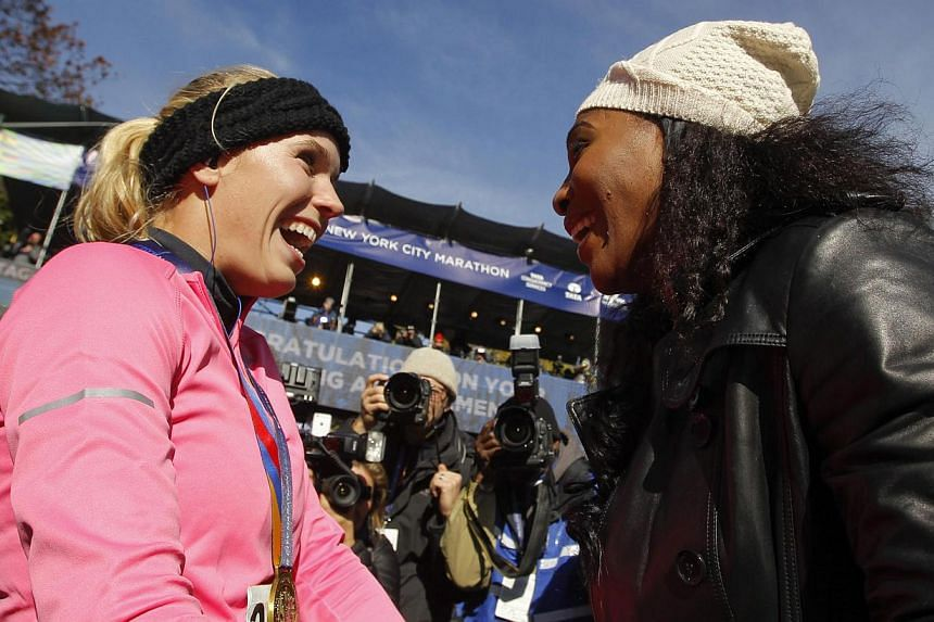 Tennis player Caroline Wozniacki (left) of Denmark is congratulated by US tennis player Serena Williams at the finish line of the New York City Marathon in New York on Nov 2, 2014. -- PHOTO: REUTERS