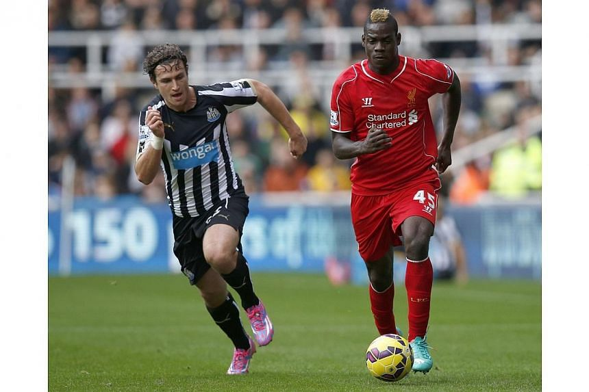 Newcastle United's Daryl Janmaat (left) challenges Liverpool's Mario Balotelli during their English Premier League football match at St James' Park in Newcastle, northern England on Nov 1, 2014. -- PHOTO: REUTERS
