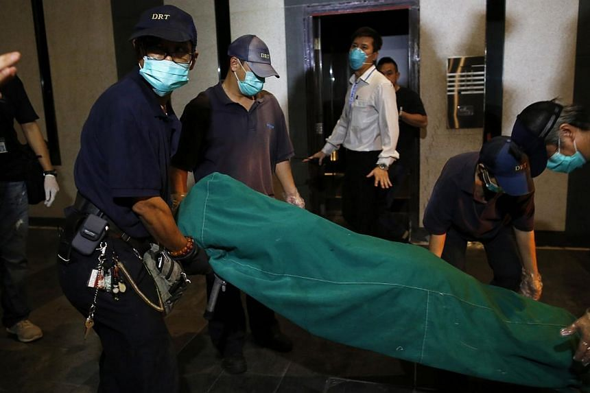 Government workers remove the body of a female found dead at a residential flat at Hong Kong's Wanchai district on Nov 1, 2014. -- PHOTO: REUTERS