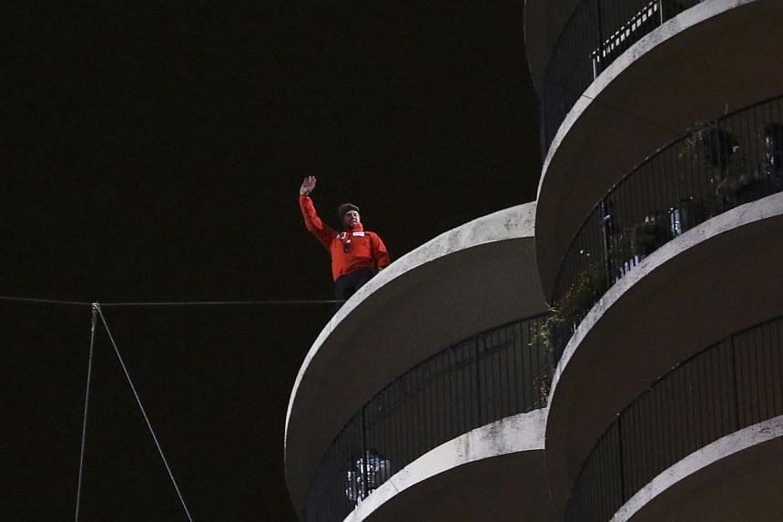 Daredevil Nik Wallenda waves after completing his blindfolded walk along a tightrope between two skyscrapers suspended 500 feet (152.4 meters) above the Chicago River in Chicago, Illinois, Nov 2, 2014. -- PHOTO: REUTERS