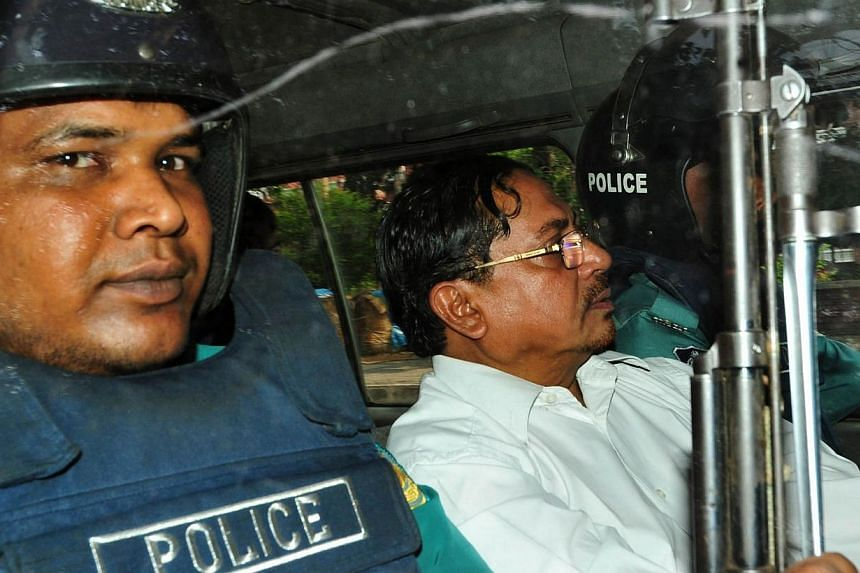 In this photograph taken on May 9, 2013, Bangladeshi Jamaat-e-Islami leader, Mohammad Kamaruzzaman, (right) sits next to a police officer as he leaves court in Dhaka.Violence broke out in Bangladesh on Monday after the country's highest court u