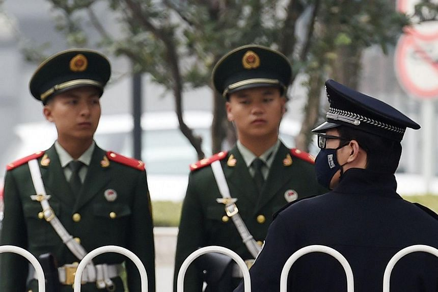 A Chinese police officer (right) stands guard with paramilitary police officers on a sidewalk in central Beijing on Oct 20, 2014, on the day the Communist Party opened a major plenum meeting.China has passed an anti-espionage law that could wid