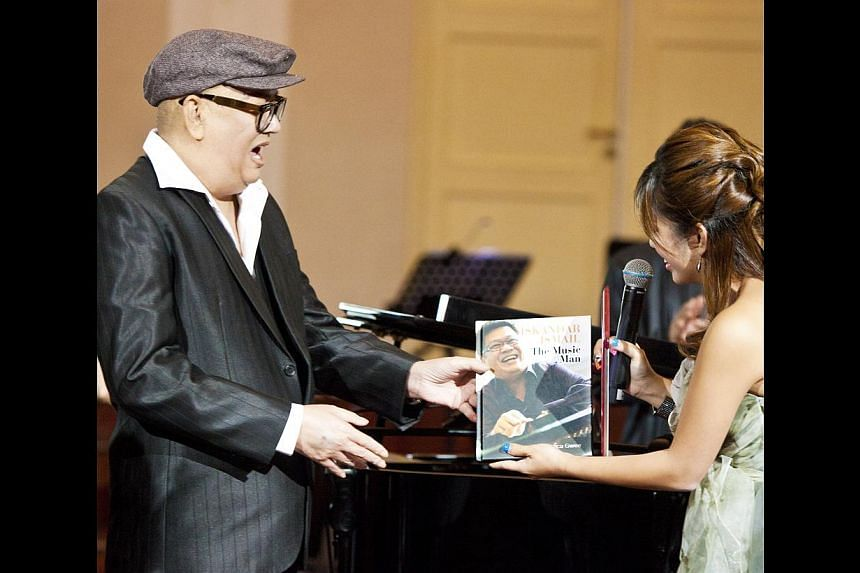 HIGHLIGHTS OF HIS LIFE: Cultural Medallion recipient Iskandar presented with the award by then President S R Nathan in 2008 and the composer (above) receiving a copy of his autobiography, Iskandar Ismail: The Music Man, from his daughter Valerie duri