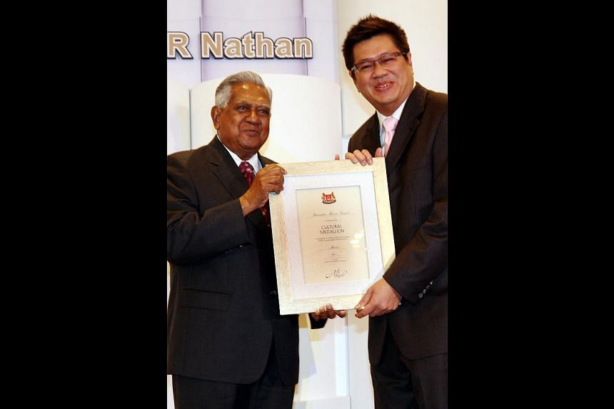 HIGHLIGHTS OF HIS LIFE: Cultural Medallion recipient Iskandar presented with the award by then President S R Nathan in 2008 (above) and the composer receiving a copy of his autobiography, Iskandar Ismail: The Music Man, from his daughter Valerie duri