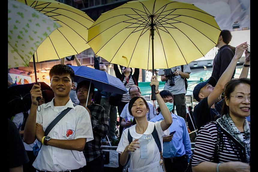 Occupy Central protesters opening their umbrellas to mark one month since they took to the streets last Tuesday in Mongkok. The members of the so-called Occupy Central Generation are drawn from the cohorts born during and since the 1980s, mostly stud